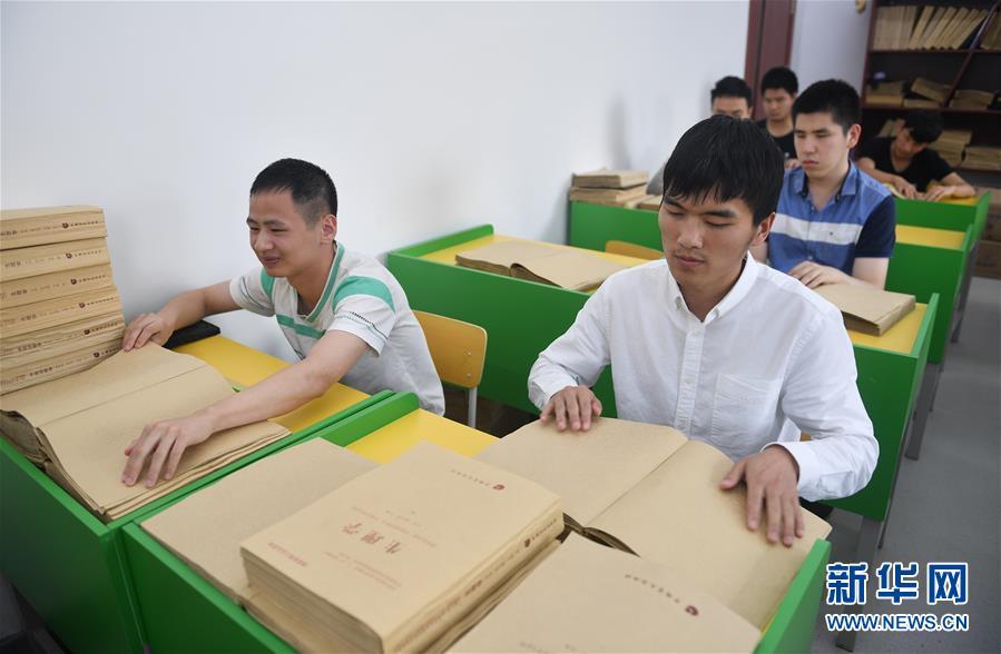 """孙东远(前右)、范长杰(前左)在教室内通过触摸""""阅读""""盲文教材(6月20日摄)。新华社记者 许畅 摄"""